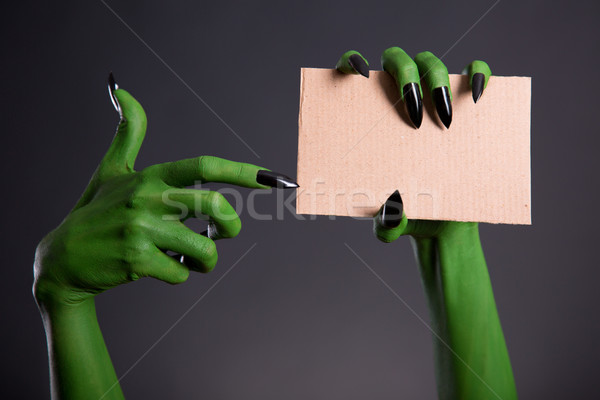 Green monster hand with black nails pointing on blank piece of c Stock photo © Elisanth