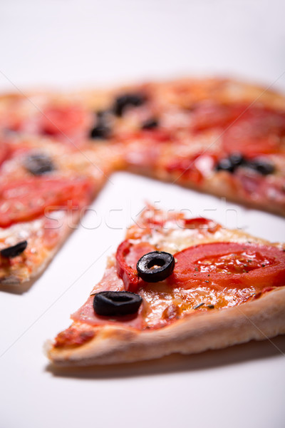 Italian pizza with ham, tomatoes and olives with a slice removed Stock photo © Elisanth