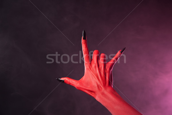 Red devil hand with black nails showing heavy metal symbol  Stock photo © Elisanth