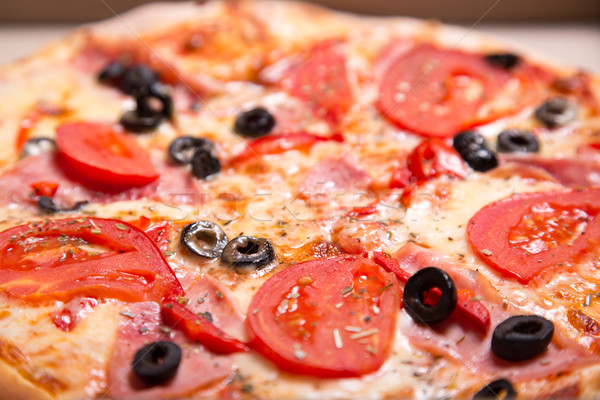 Close-up shot of Italian pizza with ham, tomatoes and olives  Stock photo © Elisanth