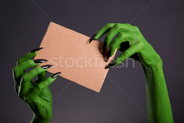 Green hands with long black nails holding empty piece of cardboa Stock photo © Elisanth