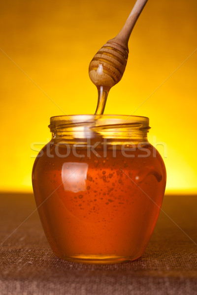 Honey jar with dipper and flowing honey  Stock photo © Elisanth