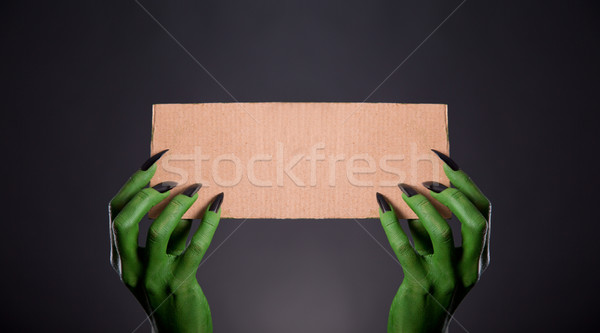 Green monster hands with black nails holding empty piece of card Stock photo © Elisanth