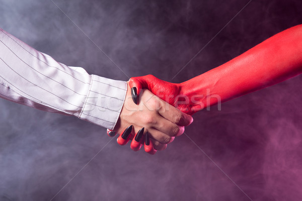 Businessman making a deal with devil  Stock photo © Elisanth