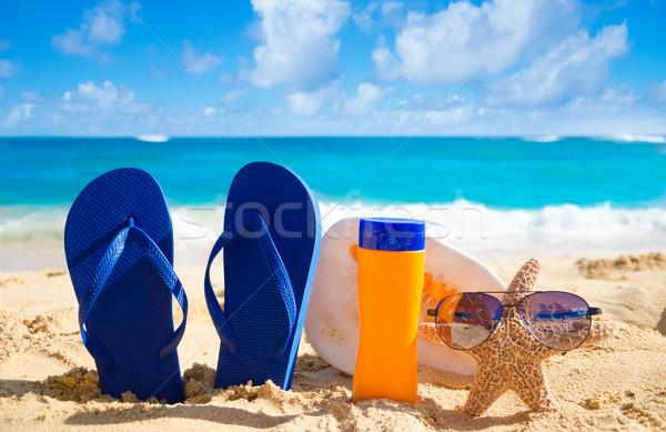 Flip flops, seashell, sunscreen and starfish with sunglasses on  Stock photo © EllenSmile