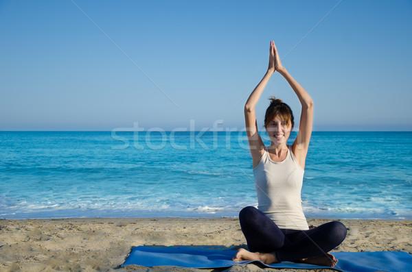 Yang woman practicing yoga by the ocean  Stock photo © EllenSmile