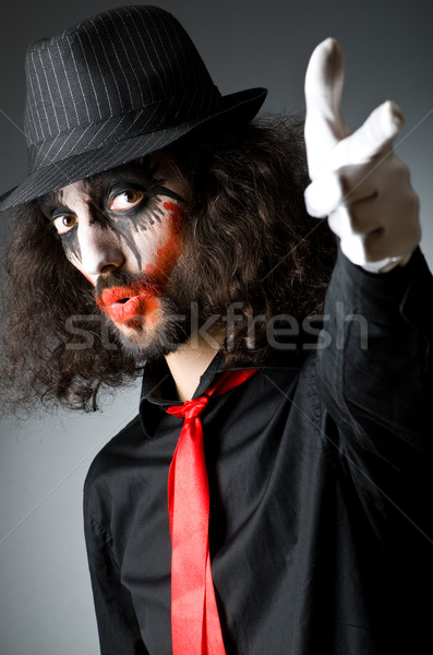 Joker personification with man in dark room Stock photo © Elnur