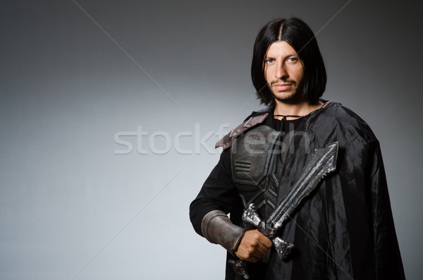 Stock photo: Angry knight with sword against dark background