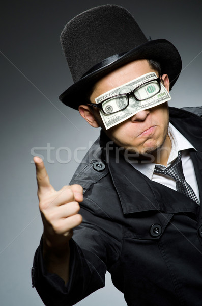 Young man in black coat holding money against gray Stock photo © Elnur