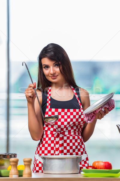 Female cook preparing soup in brightly lit kitchen Stock photo © Elnur