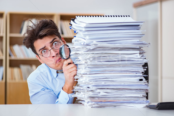 Funny auditor checking reports with magnifying glass Stock photo © Elnur