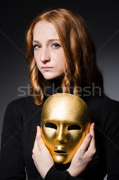 Redhead woman iwith mask in hypocrisy consept against grey backg Stock photo © Elnur