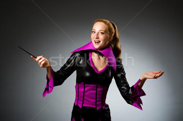 Female magician doing tricks on grey background Stock photo © Elnur
