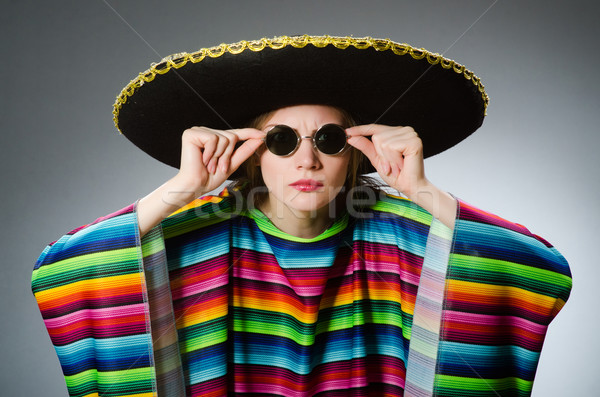 Girl in mexican vivid poncho against gray Stock photo © Elnur