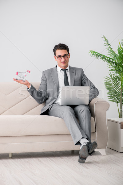 Businessman with laptop and shopping cart Stock photo © Elnur