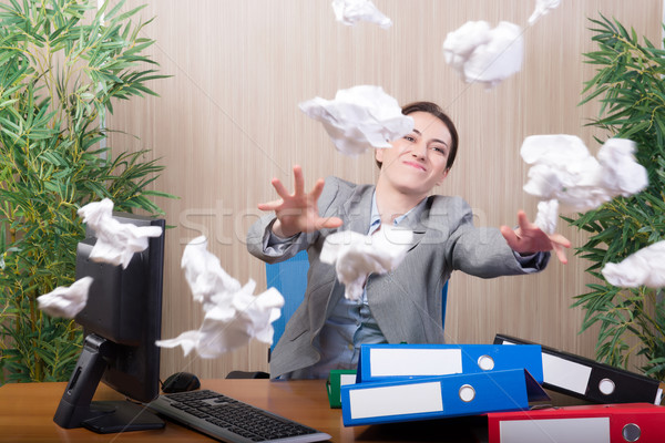 Woman under stress tossing papers in the office Stock photo © Elnur