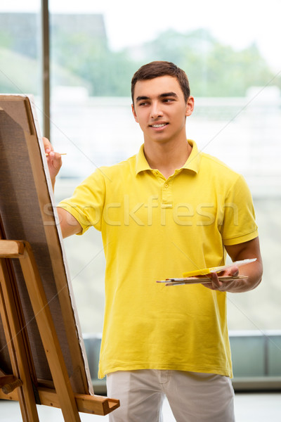 The young male artist drawing pictures in bright studio Stock photo © Elnur