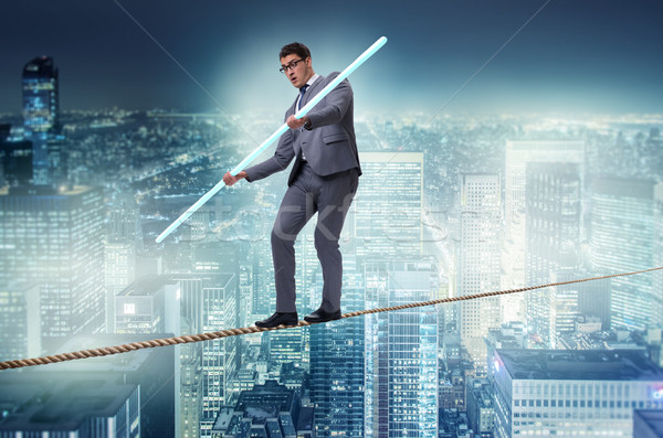 Businessman doing tightrope walking in risk concept Stock photo © Elnur