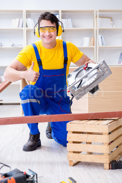 Repairman carpenter cutting sawing a wooden plank with a circula Stock photo © Elnur