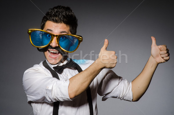 Young man with false moustache and large sunglasses isolated on gray Stock photo © Elnur
