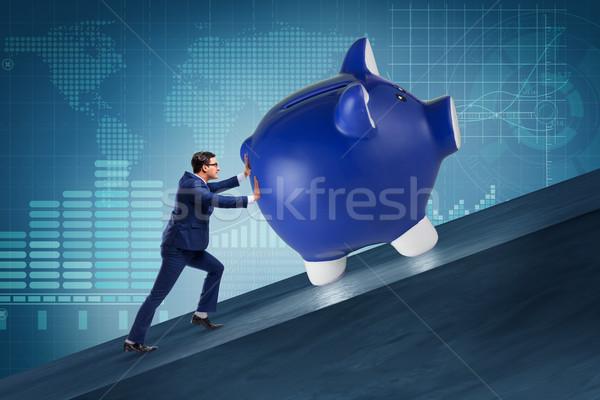 Man pushing piggybank uphill in business concept Stock photo © Elnur