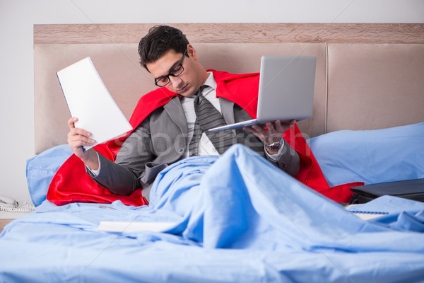 Super hero businesswoman working in bed Stock photo © Elnur