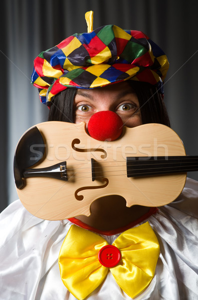 Funny clown plyaing violin against curtain Stock photo © Elnur
