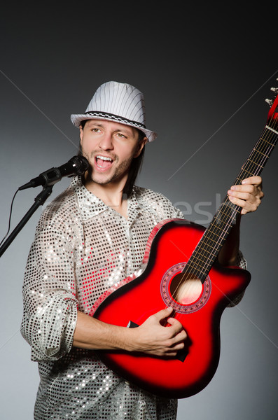 Man with guitar singing with microphone Stock photo © Elnur