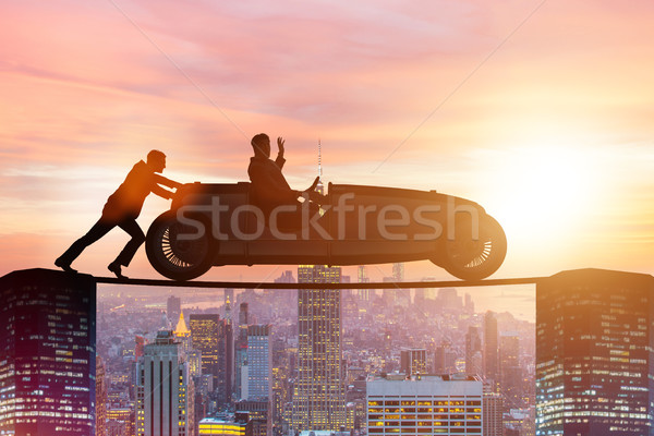 Teamwork concept with businessman pushing car Stock photo © Elnur