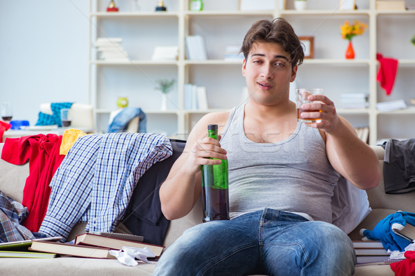 The young man student drunk drinking alcohol in a messy room Stock photo © Elnur
