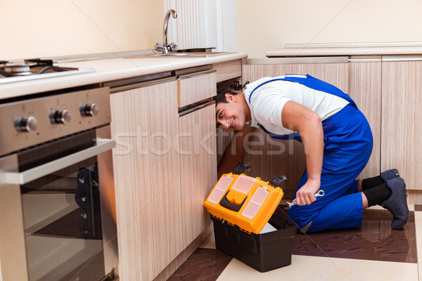 Young repairman working at the kitchen Stock photo © Elnur