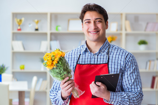 Flower shop assistant offering a bunch of flowers Stock photo © Elnur