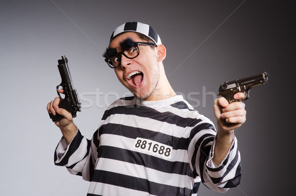 Funny prisoner with weapon isolated on gray Stock photo © Elnur
