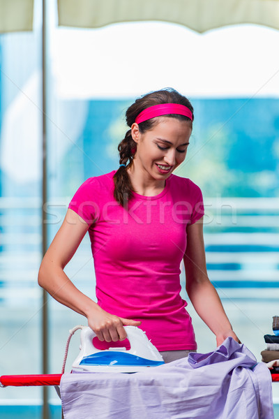Young woman ironing clothing on board Stock photo © Elnur