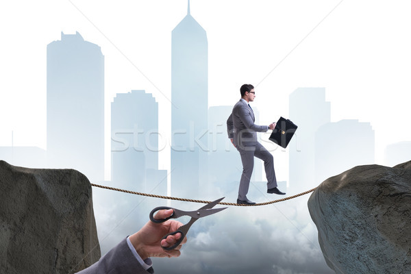 Hand cutting the rope under businessman tightrope walker Stock photo © Elnur