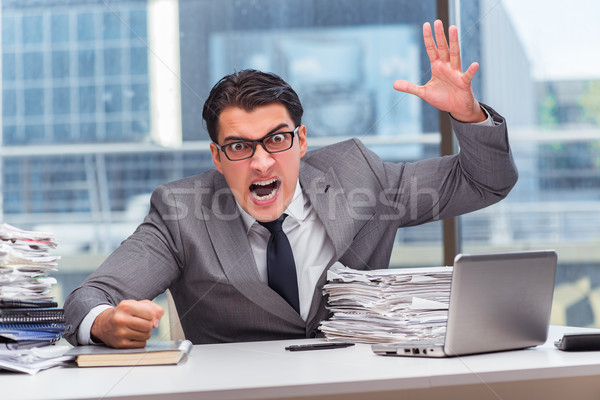 Angry businessman with too much work in office Stock photo © Elnur