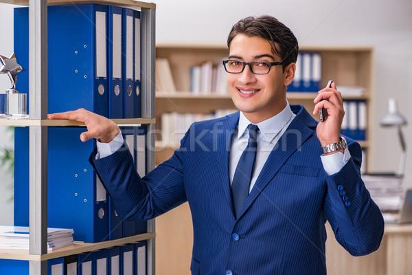 Fiatalember áll polc mappák iroda üzletember Stock fotó © Elnur