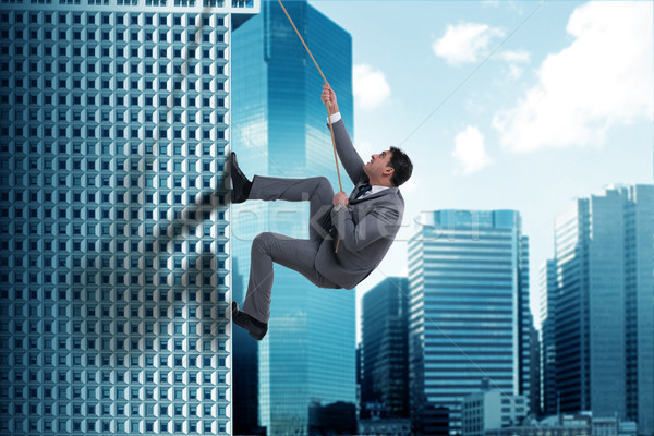 Businessman in challenge concept climbing skyscraper Stock photo © Elnur