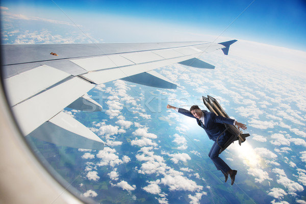 Businessman flying next to commercial flight Stock photo © Elnur