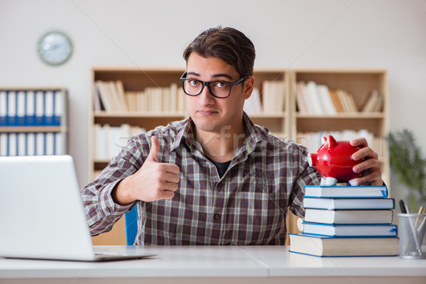 Young student breaking piggy bank to buy textbooks Stock photo © Elnur