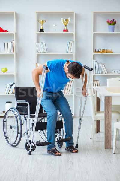 Young man recovering after surgery at home with crutches and a w Stock photo © Elnur