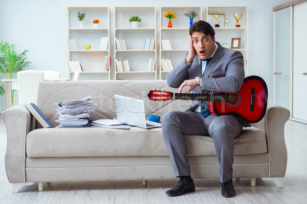 Businessman playing guitar at home Stock photo © Elnur