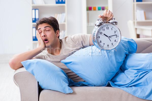 Man having trouble waking up with alarm clock Stock photo © Elnur