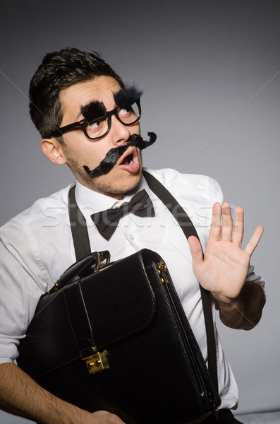 Stock photo: Young man with false moustache isolated on gray