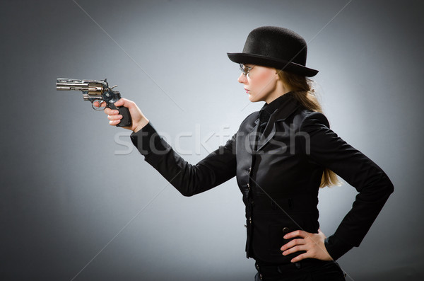 Female spy with weapon against gray Stock photo © Elnur