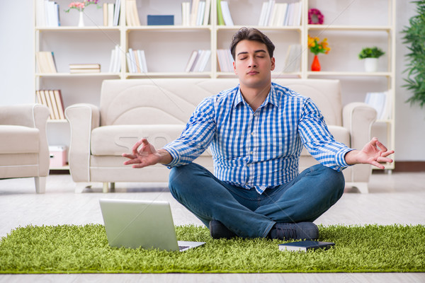 Young handsome man sitting on floor at home Stock photo © Elnur
