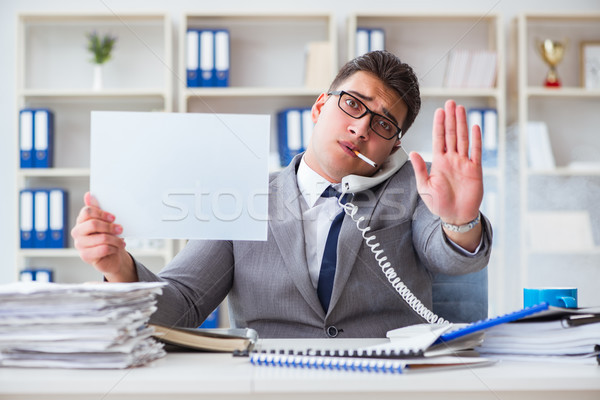 Businessman smoking at work in office holding a blank message bo Stock photo © Elnur