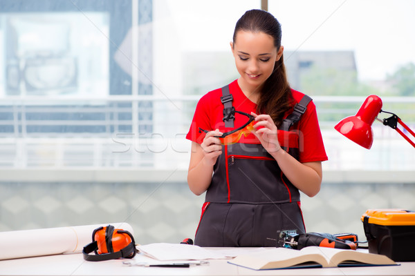 Stock photo: The young woman in coveralls doing repairs
