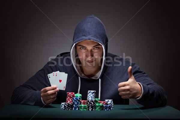 Young man wearing a hoodie with cards and chips gambling Stock photo © Elnur