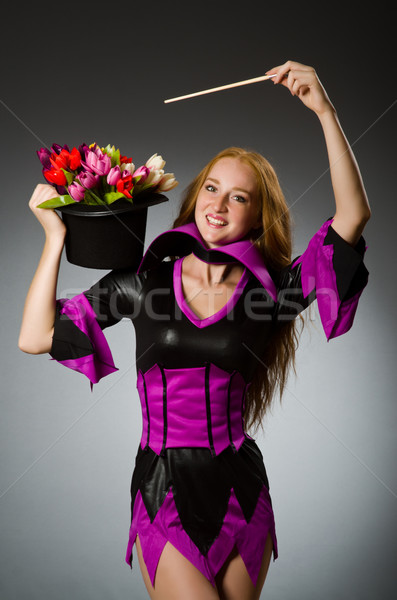 Female magician doing tricks on grey background Stock photo © Elnur